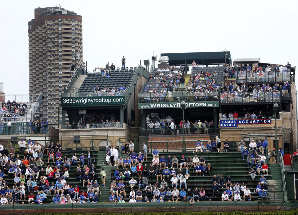 FILE - This May 17, 2013 file photo shows spectators watching a Chicago Cubs baseball game from several of the rooftop bleachers across the field from Wrigley Field in Chicago. The owners of the Chicago Cubs say they're moving forward with plans to renovate and expand Wrigley Field, despite the threat of lawsuits by the owners of the adjacent rooftop venues overlooking the 100-year-old ballpark. Chairman Tom Ricketts, whose family owns the north-side Chicago team, said Thursday, May 22, 2014, that the Cubs will submit a revised expansion plan to the Commission on Chicago Landmarks that includes the team's original proposal to add several outfield signs and additional bleacher seats.  (AP Photo/Charles Rex Arbogast, File)