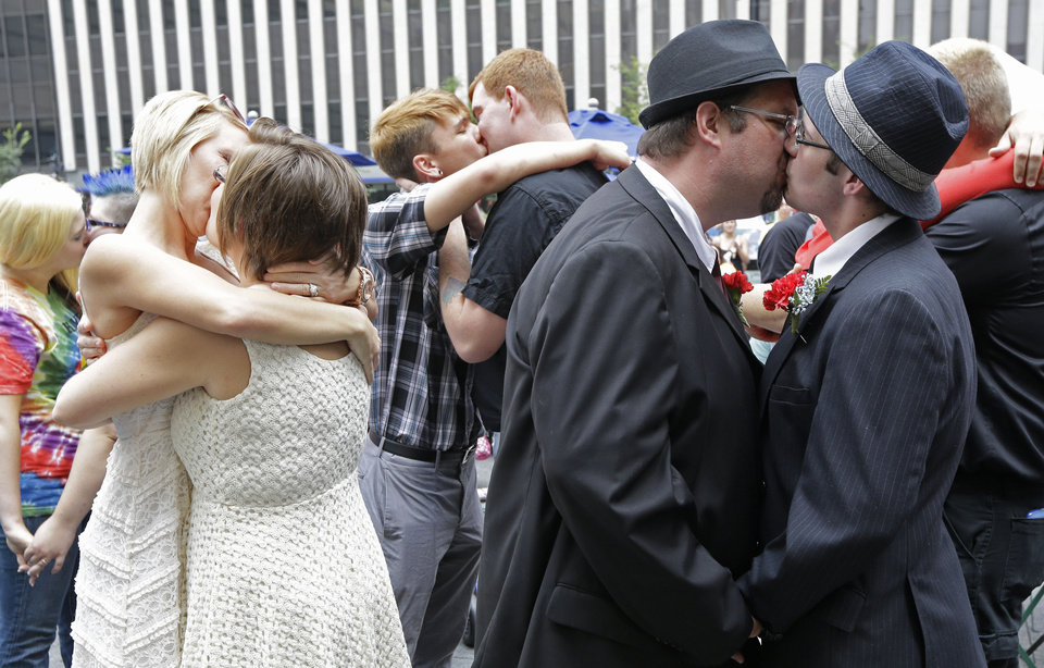 Photo - Several gay couples kiss after they were united in a commitment ceremony, Wednesday, Aug. 6, 2014, on Fountain Square in Cincinnati. Three judges of the 6th U.S. Circuit Court of Appeals in Cincinnati are set to hear arguments Wednesday in six gay marriage fights from four states, Kentucky, Michigan, Ohio and Tennessee. (AP Photo/Al Behrman)