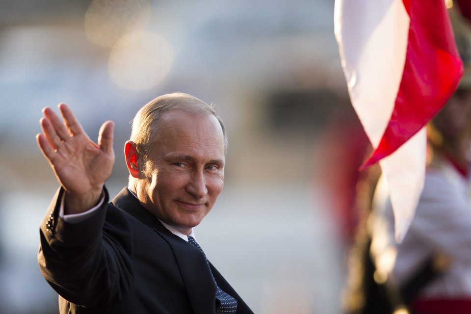 Photo - Russia's President Vladimir Putin waves to photographer as he leaves the Itamaraty Palace after attending the final day of the BRICS Summit in Brasilia, Brazil, Wednesday, July 16, 2014. (AP Photo/Felipe Dana)