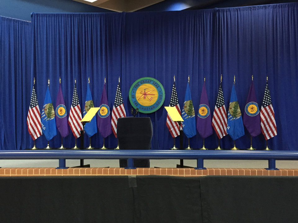Photo - The seal of the Choctaw Nation, flanked by the national and state flags, form the backdrop for the podium where President Obama will speak later today.