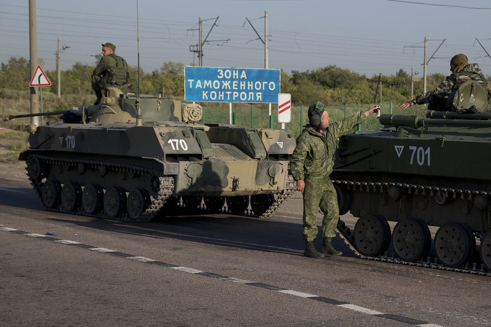 Photo - Russian solders with their several military vehicle gather at the rail road crossing about 30 kilometers (19 miles) from Ukrainian border at  Rostov-on-Don region, Russia, early Friday, Aug. 15, 2014. The sigh reads