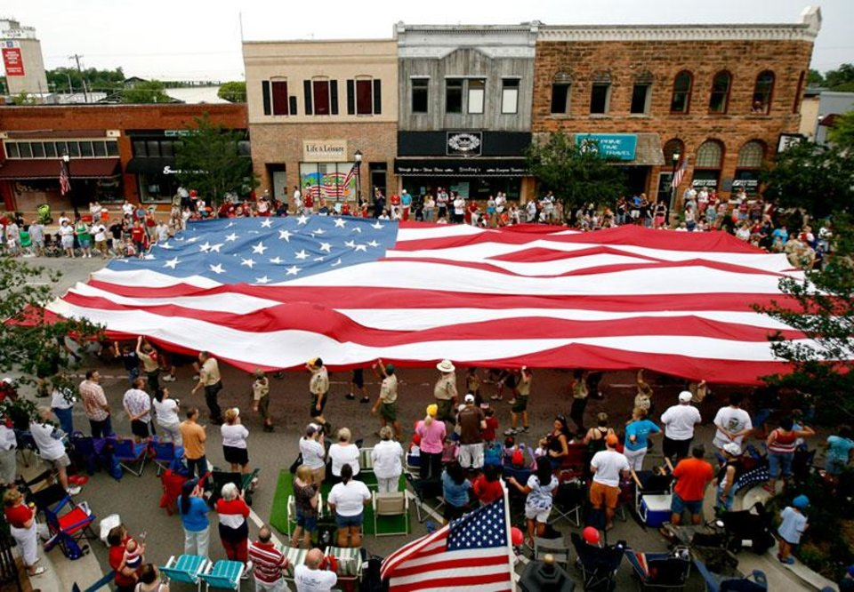 Photo -  Boy Scouts carry an American flag down Broadway in Edmond, Okla., during the LibertyFest Parade Saturday, July 4, 2009. Photo by Bryan Terry, The Oklahoman