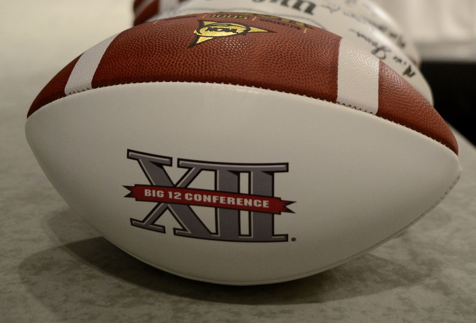 Big 12 football sit next to the podium as Oklahoma State head coach Mike Gundy answers questions during NCAA college football Big 12 Media Days, Monday, July 25, 2011, in Dallas. (AP Photo/Matt Strasen) ORG XMIT: TXMS111