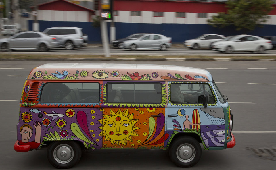 Photo - In this Sept. 18, 2013 photo, advertising executive Marcelo Serpa drives his Volkswagen van, or Kombi, emblazoned with a