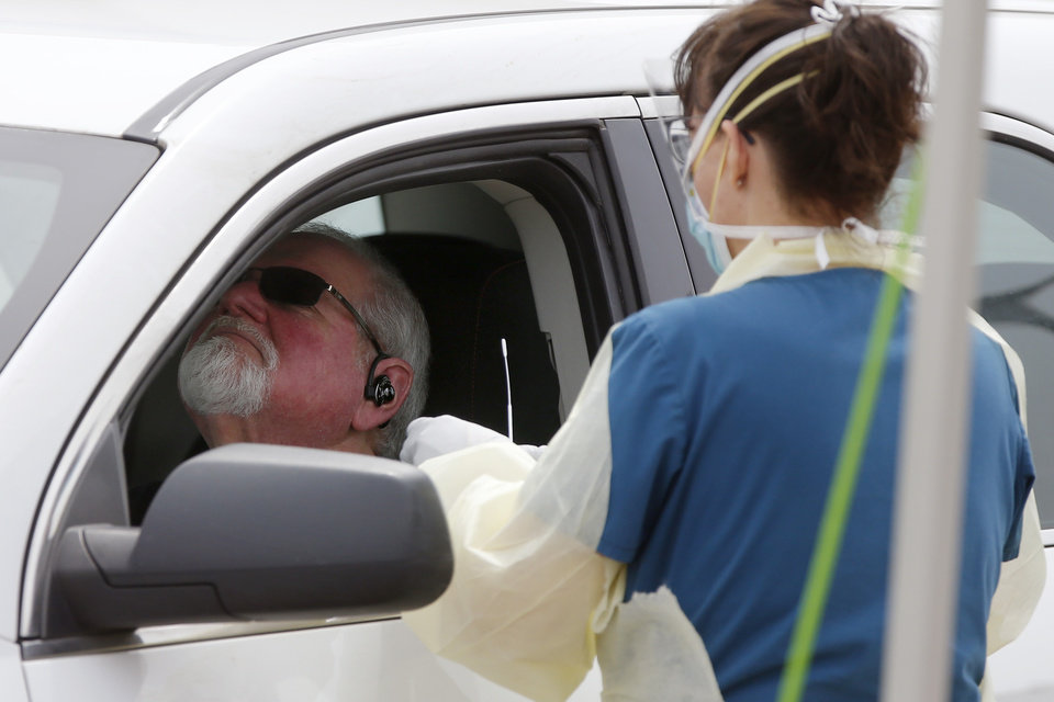 Photo - A Cleveland County Health Department employee uses a swab to collect a sample from a man at a COVID-19 drive-thru testing site at Griffin Community Park in Norman, Okla., Thursday, April 9, 2020. [Bryan Terry/The Oklahoman]