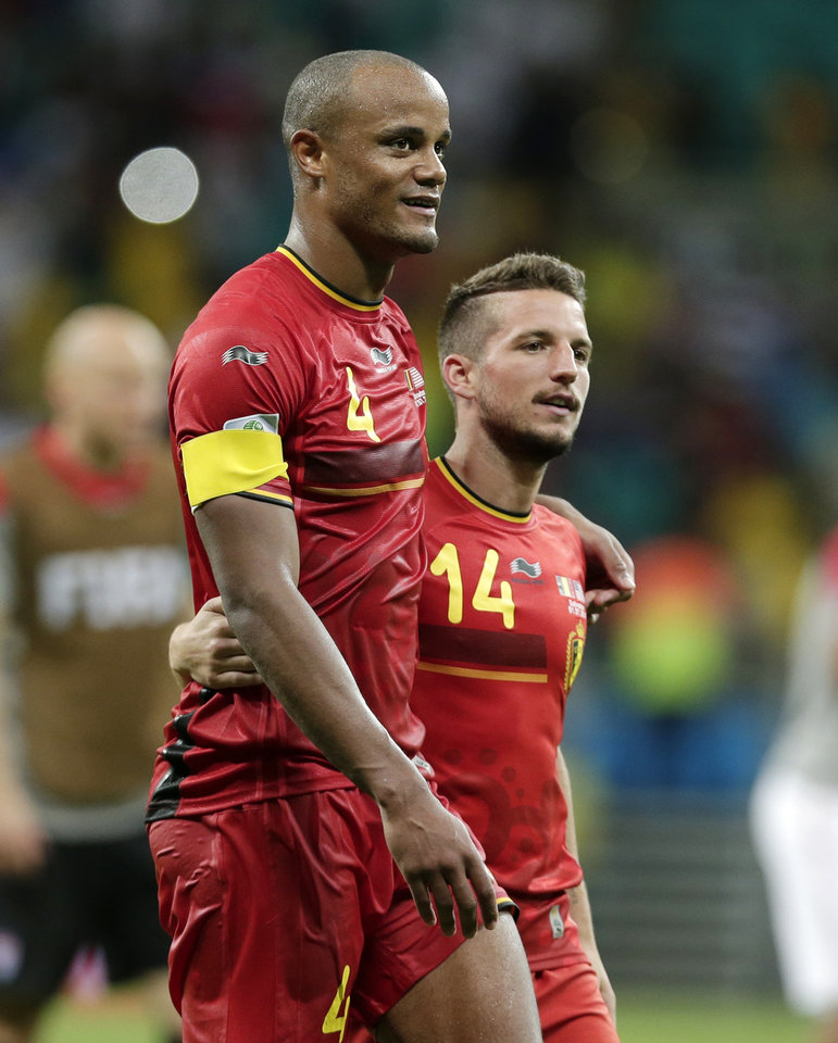 Photo - Belgium's Vincent Kompany (4) and Dries Mertens walk off the pitch after Belgium defeated the USA 2-1 in extra time to advance to the quarterfinals during the World Cup round of 16 soccer match between Belgium and the USA at the Arena Fonte Nova in Salvador, Brazil, Tuesday, July 1, 2014. (AP Photo/Marcio Jose Sanchez)