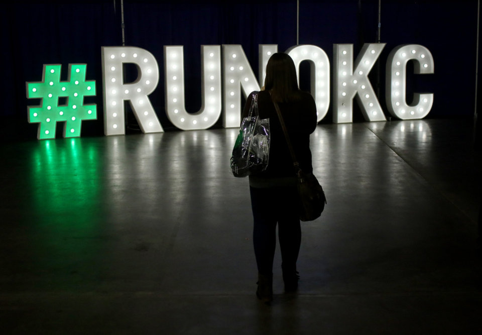 Photo -  A woman stops Friday to take a photo of the #runokc sign in the marathon expo at the Cox Convention Center. [Photo by Doug Hoke, The Oklahoman]