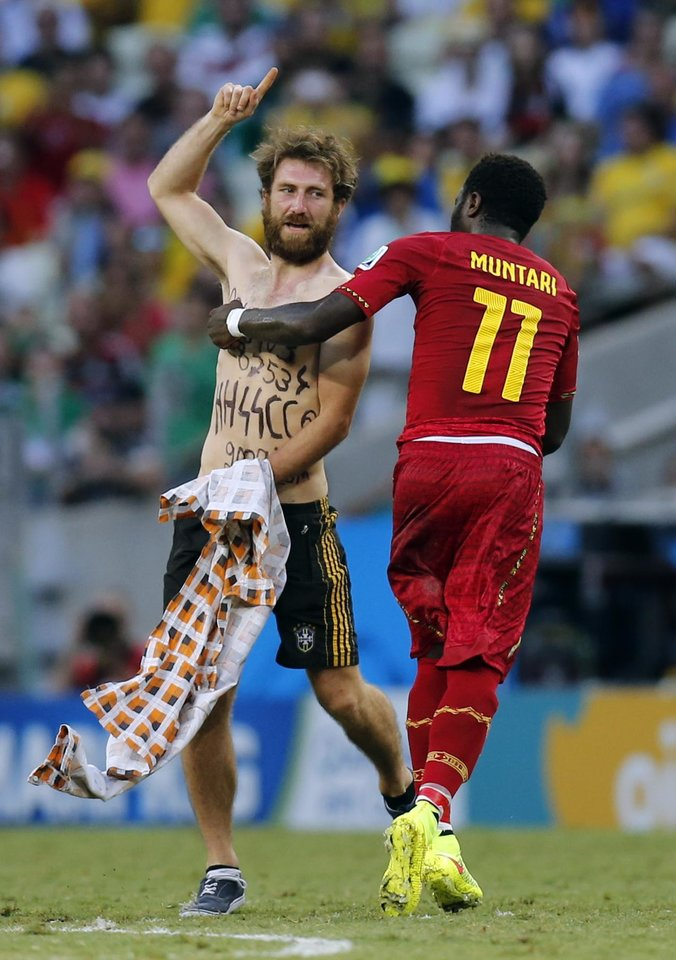 Photo - Ghana's Sulley Muntari assists a man off the pitch after he ran on during the group G World Cup soccer match between Germany and Ghana at the Arena Castelao in Fortaleza, Brazil, Saturday, June 21, 2014. (AP Photo/Frank Augstein)