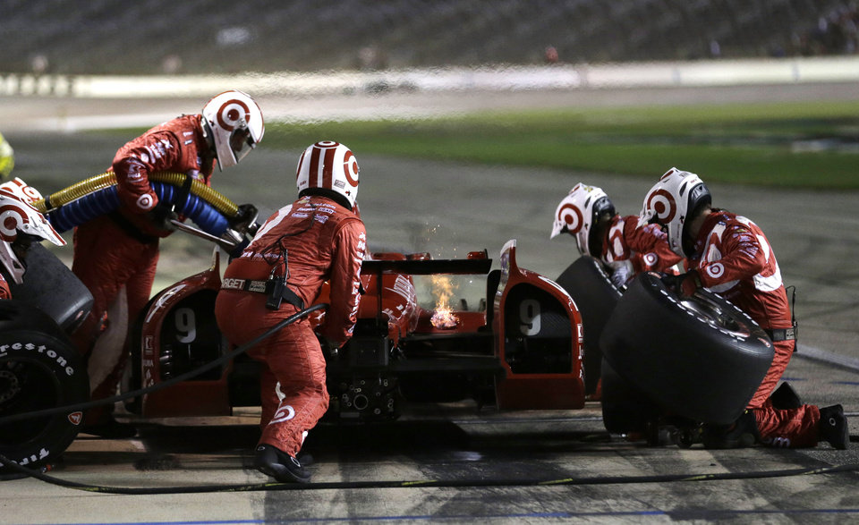 Photo - Scott Dixon, of New Zealand, makes a pit stop, as a small fire burns during an IndyCar auto race at Texas Motor Speedway in Fort Worth, Texas, Saturday, June 7, 2014.  Dixon returned to racing without incident.  (AP Photo/Tim Sharp)