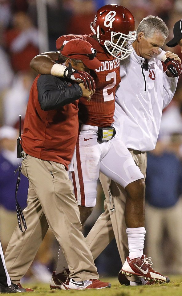 Photo - Oklahoma's Julian Wilson (2) is helped off the field with an injury during the college football game between the University of Oklahoma Sooners (OU) and the Texas Christian University Horned Frogs (TCU) at the Gaylord Family-Oklahoma Memorial Stadium on Saturday, Oct. 5, 2013 in Norman, Okla.   Photo by Chris Landsberger, The Oklahoman