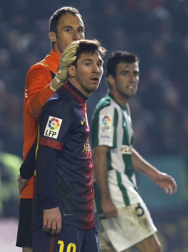 Barcelona's Lionel Messi, front, and Cordoba's goalkeeper Mikel Saizar, left, look on during the 1st leg of a last-16 Copa del Rey soccer match at Arcangel stadium in, Cordoba, Spain on Wednesday, Dec. 12, 2012. (AP Photo/Angel Fernandez)