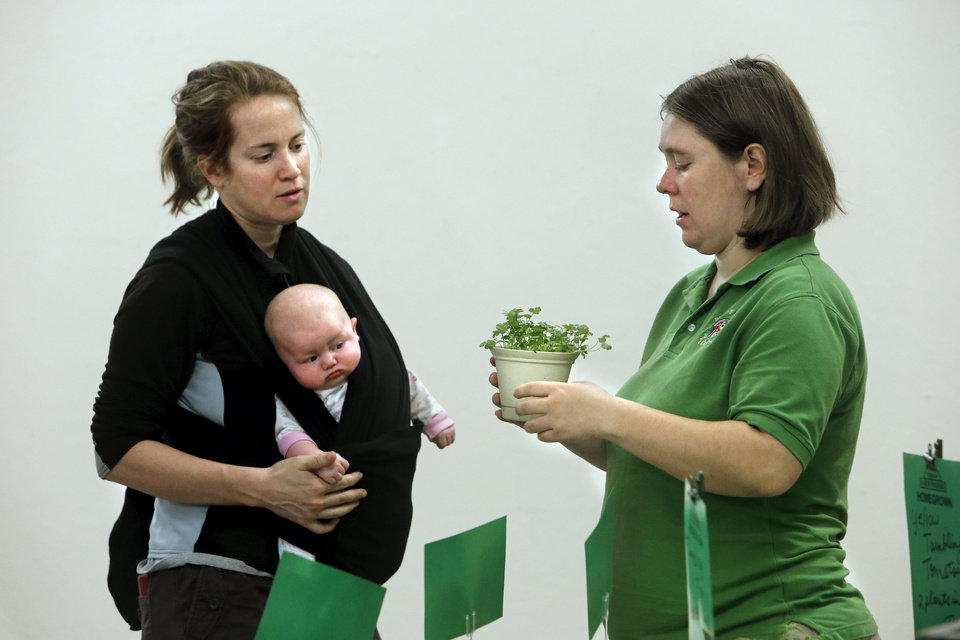 Below right: Tobi Perry, right, shows a cilantro plant to Amy Cerato and daughter Sophie, 10 weeks, at the Norman Farm Market.
