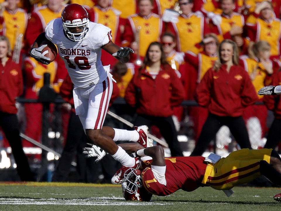 Photo - Oklahoma's Justin Brown (19) leaps over Iowa State's Cliff Stokes (7) during a college football game between the University of Oklahoma (OU) and Iowa State University (ISU) at Jack Trice Stadium in Ames, Iowa, Saturday, Nov. 3, 2012. Photo by Bryan Terry, The Oklahoman