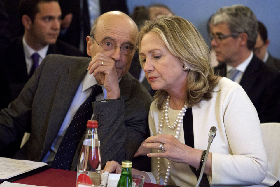 Photo -   Secretary of State Hillary Rodham Clinton speaks with France's Foreign Minister Alain Juppe during a meeting on Syria, Thursday, April 19, 2012, in Paris. (AP Photo/Jacquelyn Martin, Pool)