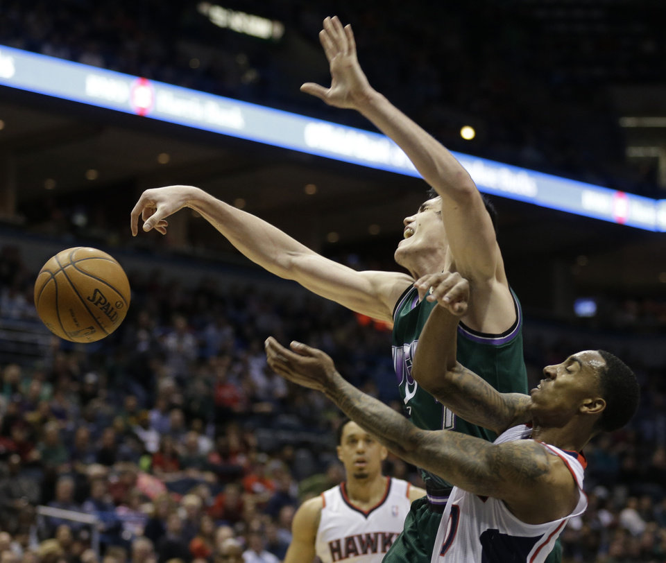 Milwaukee Bucks' Ersan Ilyasova, top, looses the ball against Atlanta Hawks' Jeff Teague, right, during the second half of an NBA basketball game, Saturday, Feb. 23, 2013, in Milwaukee. (AP Photo/Jeffrey Phelps)