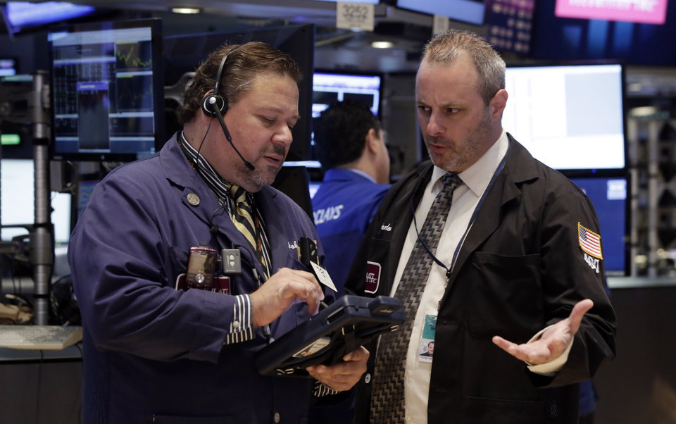 Photo - Trader John Santiago, left, talks with a colleague on the floor of the New York Stock Exchange Monday, June 23, 2014. Stocks are edging lower in early trading after indexed closed last week at record highs. (AP Photo/Richard Drew)