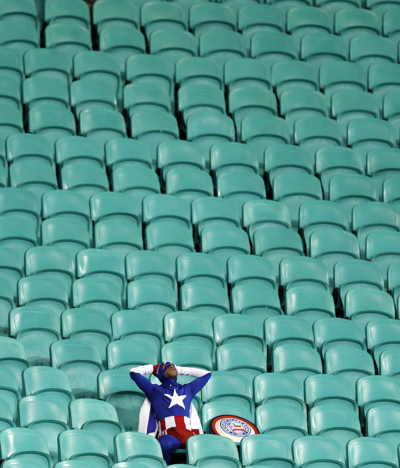 Photo - 10ThingstoSeeSports - A lone U.S. supporter dressed as 'Captain America' sits in the stands after Belgium defeated the U.S. 2-1 in extra time to advance to the quarterfinals during the World Cup round of 16 soccer at the Arena Fonte Nova in Salvador, Brazil, Tuesday, July 1, 2014. (AP Photo/Natacha Pisarenko, File)