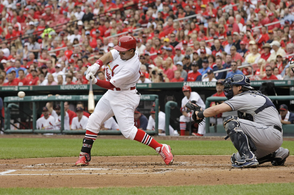 Photo - St. Louis Cardinals' Jon Jay (19) connects for a two-RBI single as San Diego Padres catcher Yasmani Grandal watches in the first inning of a baseball game, Sunday, Aug. 17, 2014, in St. Louis. (AP Photo/Tom Gannam)