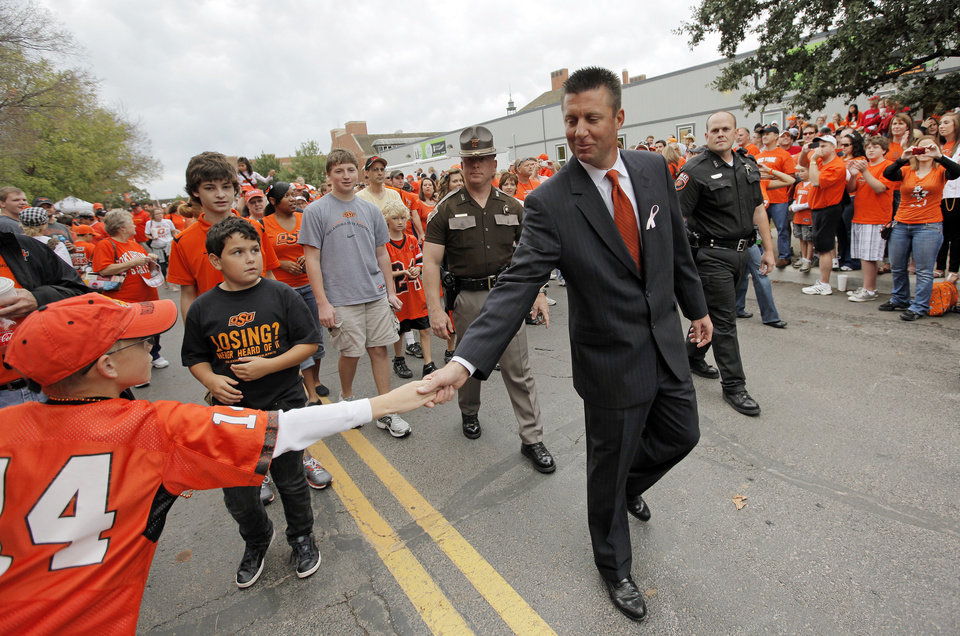 Photo - OSU head coach Mike Gundy greets a fan during the Spirit Walk before the college football game between the Oklahoma State Cowboys (OSU) and the Nebraska Huskers (NU) at Boone Pickens Stadium in Stillwater, Okla., Saturday, Oct. 23, 2010. Photo by Nate Billings, The Oklahoman