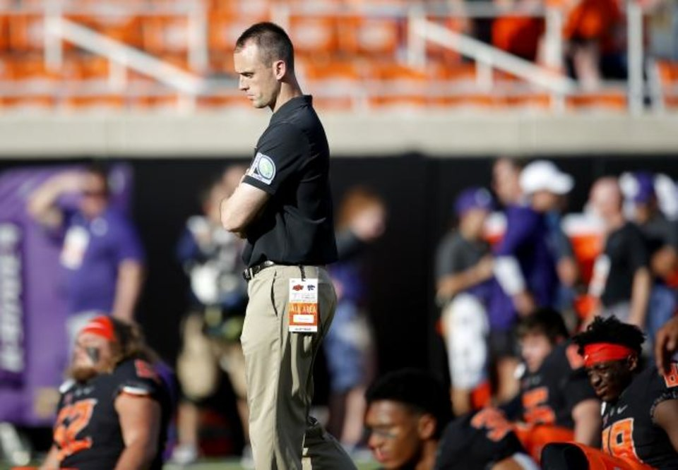 Photo -  OSU offensive coordinator Sean Gleeson watches his team stretch before facing Kansas State on Sept. 27 in Stillwater. [Sarah Phipps/The Oklahoman]