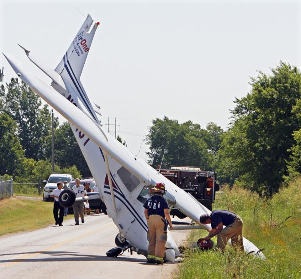 Photo -  AIRPLANE CRASH: An Air One Flight Academy plane stand on its nose on NW 122nd near Sara Road after it skidded off the end of a runway at Sun Dance Airport, Wednesday,  June 24, 2009. Photo By David McDaniel, The Oklahoman. ORG XMIT: KOD