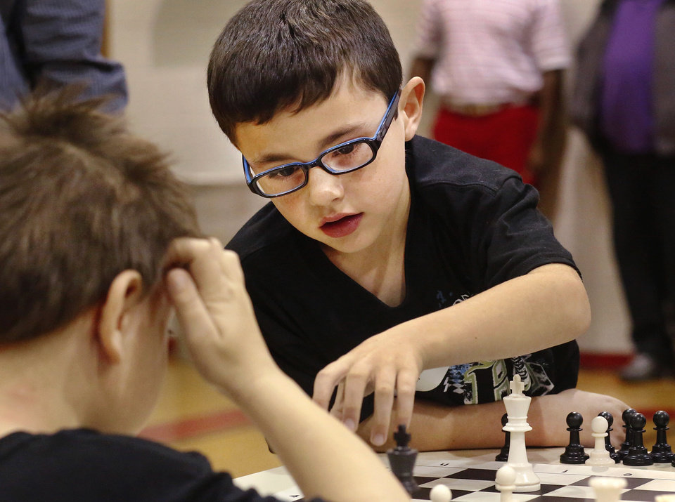 Alexander Bonner moves his chess piece as Gage Crowson considers his next move. Bonner is a first-grader at Cleveland Bailey Elementary School. Crowson is a first-grader at Townsend Elementary School.