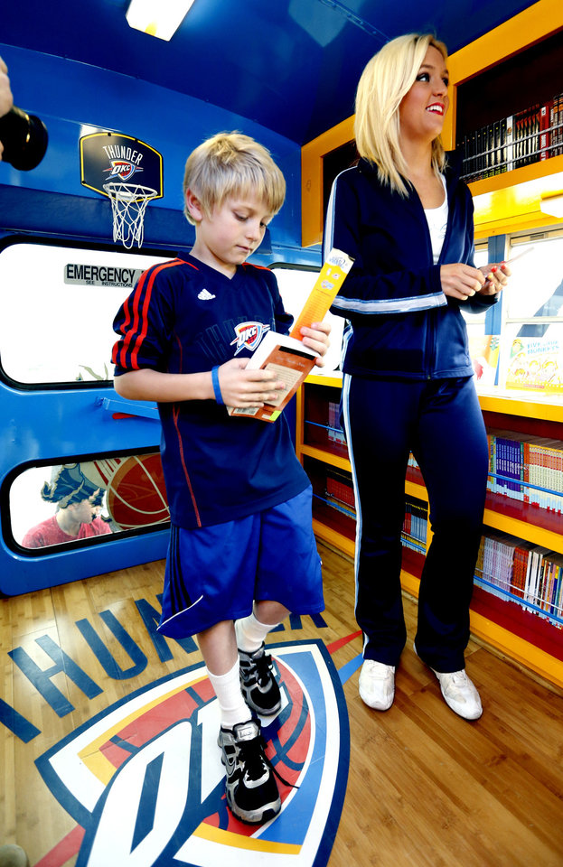 Kyzer McNew, 9, gets help from a Thunder Girl in selecting a book from the Oklahoma City Thunder's Rolling Thunder Book Bus, which made a stop Tuesday at the Cleveland County YMCA's spring break camp. PHOTO BY STEVE SISNEY, THE OKLAHOMAN <strong>STEVE SISNEY</strong>