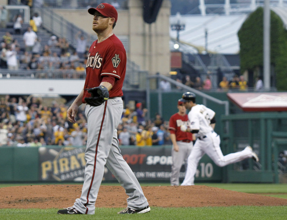 Photo -   Arizona Diamondbacks starting pitcher Ian Kennedy waits for a new baseball as Pittsburgh Pirates' Neil Walker rounds the bases behind him after hitting a three-run home run in the first inning of a baseball game Wednesday, Aug. 8, 2012, in Pittsburgh. (AP Photo/Keith Srakocic)