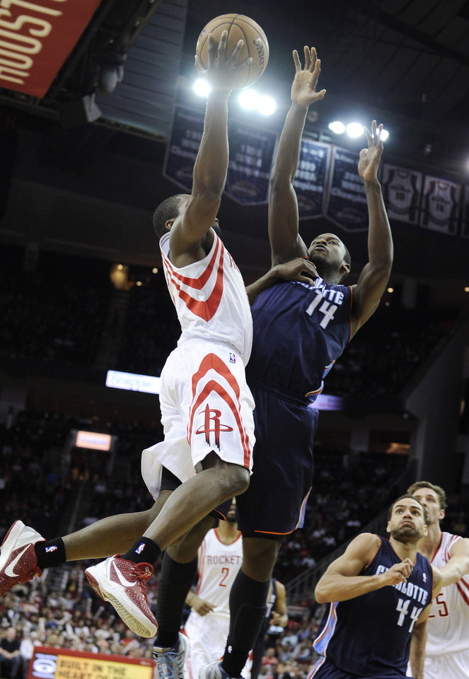 Houston Rockets\' Toney Douglas, left, and Charlotte Bobcats\' Michael Kidd-Gilchrist (14) collide under the basket in the second half of an NBA basketball game on Saturday, Feb. 2, 2013, in Houston. Kidd-Gilchrist took a hard fall and left the court on a stretcher. (AP Photo/Pat Sullivan)
