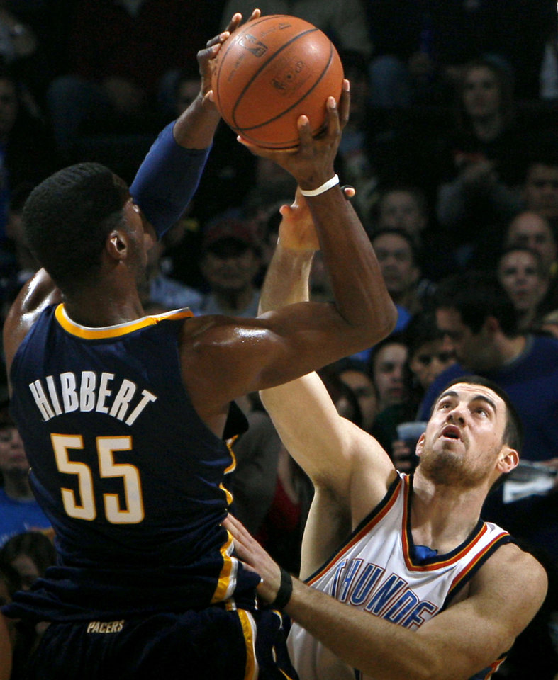 Photo - Oklahoma City's Nick Collison pressures a shot by Indiana's Roy Hibbert during the NBA basketball game between the Indiana Pacers and the Oklahoma City Thunder at the Ford Center in Oklahoma City, Sunday, April 5, 2009. Photo by John Clanton, The Oklahoman