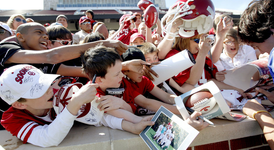 Photo - OU fans fight for position to get an autograph from Sam Bradford after Oklahoma's Red-White football game at The Gaylord Family - Oklahoma Memorial Stadiumin Norman, Okla., Saturday, April 11, 2009. Photo by Bryan Terry, The Oklahoman