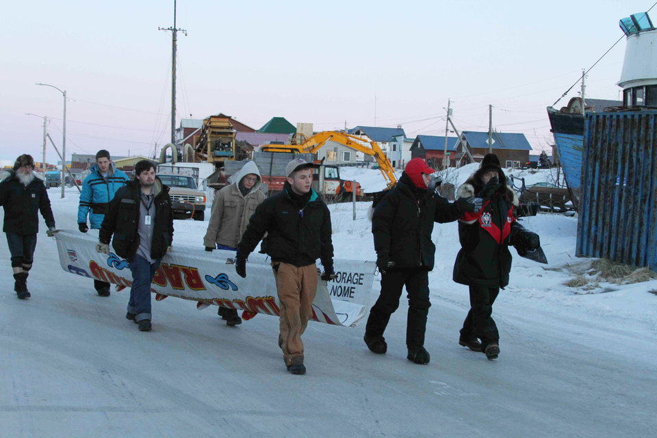 Photo - Volunteers walk the Iditarod Trial Sled Dog Race finish banner to the finish line in Nome, Alaska, on Monday, March 10, 2014. The race winner is expected some time early Tuesday, March 11, 2014. (AP Photo/Mark Thiessen)