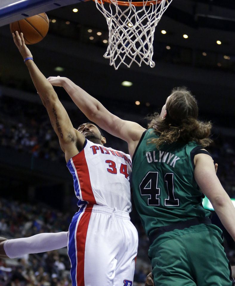 Photo - Boston Celtics center Kelly Olynyk (41) defends a shot by Detroit Pistons guard Peyton Siva (34) during the first half of an NBA basketball game Saturday, April 5, 2014, in Auburn Hills, Mich. (AP Photo/Duane Burleson)