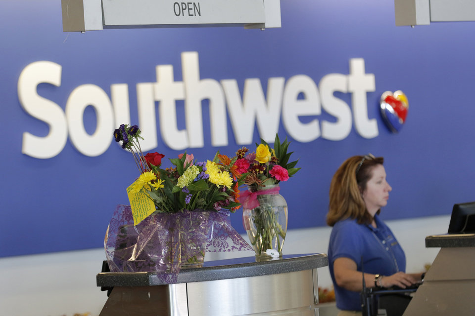 Photo -  Flower bouquets are displayed Wednesday at the Southwest Airlines ticket counter at Will Rogers World Airport. Southwest Airlines employee Michael Winchester, 52, was shot to death on Tuesday. [Photo By Steve Gooch, The Oklahoman]