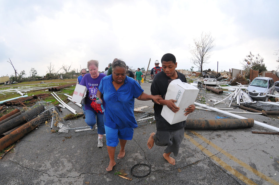 Photo - Pearline G. Hinton, left, and son Kendrell Dwayne Hinton, 16, flee the remains of their home in Rosedale after hearing word that another storm was on its way after a tornado tore through Tuscaloosa, Ala. Wednesday afternoon, April 27, 2011. (AP Photo/The Tuscaloosa News, Kelly Lambert)