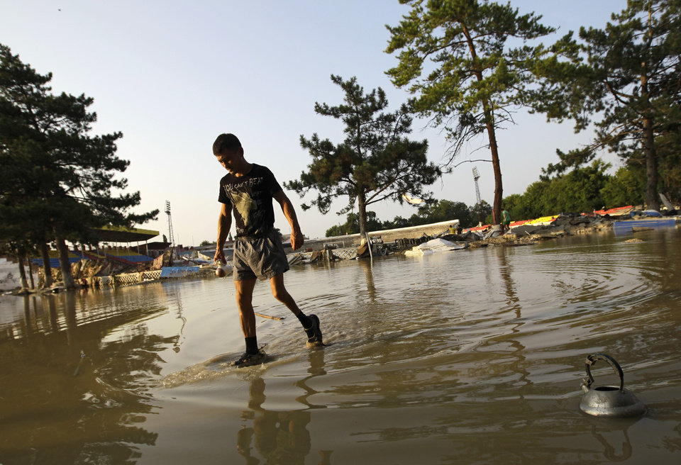 Photo -   A man walks along a flooded playground at the city stadium in Krimsk, about 1,200 kilometers (750 miles) south of Moscow, Sunday, July 8, 2012. Intense flooding in the Black Sea region of southern Russia killed at least 150 people after torrential rains dropped nearly a foot of water, forcing many to scramble out of their beds for refuge in trees and on roofs, officials said Saturday. (AP Photo/Sergey Ponomarev)