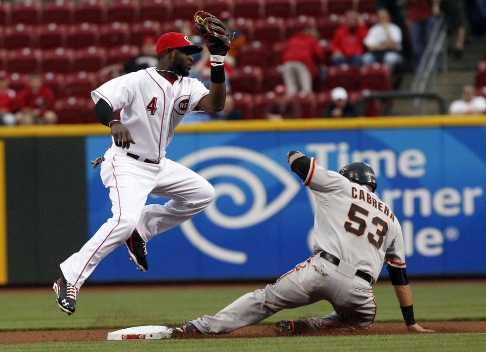 Cincinnati Reds second baseman Brandon Phillips, left, tries to tag out San Francisco Giants' Melky Cabrera who stole second base in the first inning of a baseball game on Wednesday, April 25, 2012, in Cincinnati. (AP Photo/Ernest Coleman)
