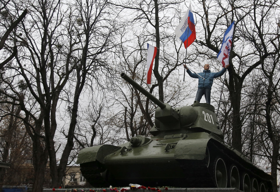 Photo - A Pro-Russian demonstrator waves Russian and Crimea flags from an old Soviet Army tank during a protest in front of a local government building in Simferopol, Crimea, Ukraine, Thursday, Feb. 27, 2014. Ukraine's acting interior minister says Interior Ministry troops and police have been put on high alert after dozens of men seized local government and legislature buildings in the Crimea region. The intruders raised a Russian flag over the parliament building in the regional capital, Simferopol, but didn't immediately voice any demands. (AP Photo/Darko Vojinovic)