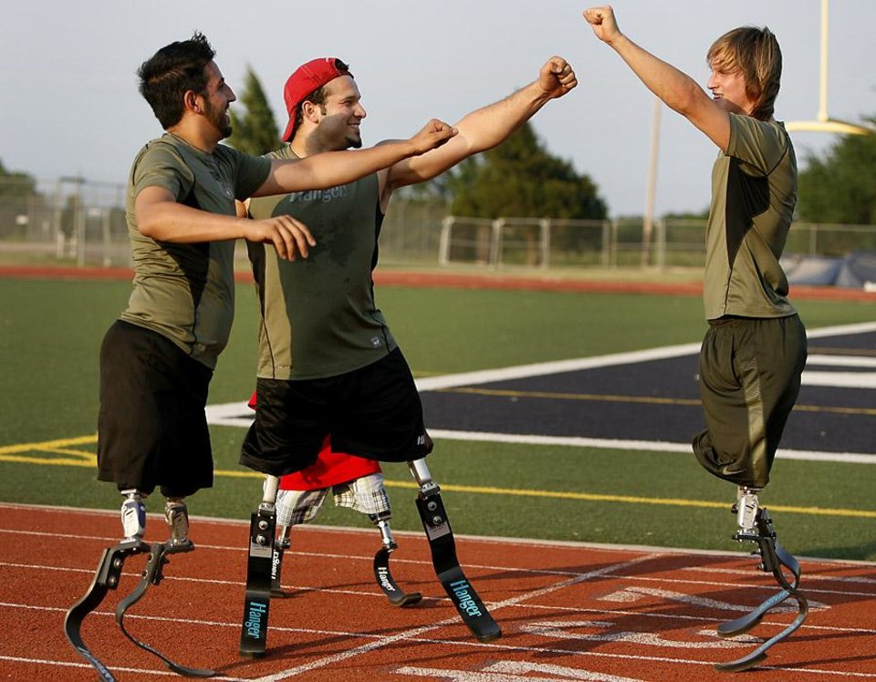Photo -  Giuseppe Chessari of Canada, left, Ugur Yumuk of Turkey and Cameron Clapp of California celebrate as they train in Edmond, Okla., Wednesday, June 8, 2011. Yumuk will be running at the Endeavor games for the first time. Photo by Bryan Terry, The Oklahoman