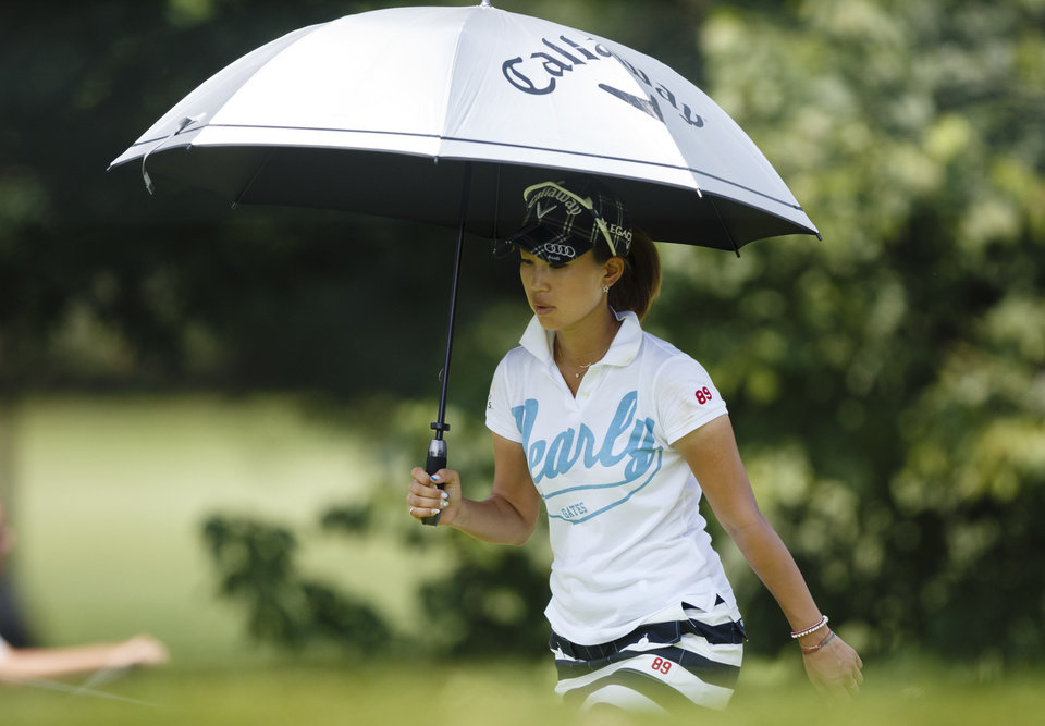Photo - Momoko Ueda, of Japan, walks up to the first green shaded by an umbrella during the second round of the Marathon Classic golf tournament at Highland Meadows Golf Club in Sylvania, Ohio, Friday, July 19, 2013. (AP Photo/Rick Osentoski)