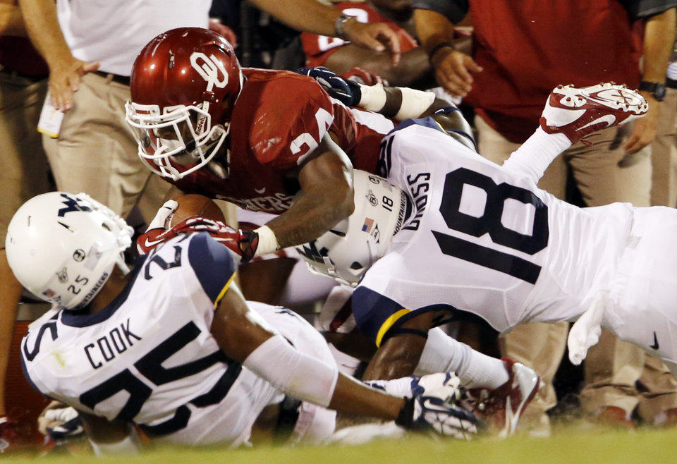 Photo - Oklahoma's Brennan Clay (24) is brought down by Darwin Cook (25) and d'Vante Henry (18) during the second half of a college football game between the University of Oklahoma Sooners (OU) and the West Virginia University Mountaineers at Gaylord Family-Oklahoma Memorial Stadium in Norman, Okla., on Saturday, Sept. 7, 2013. Photo by Steve Sisney, The Oklahoman