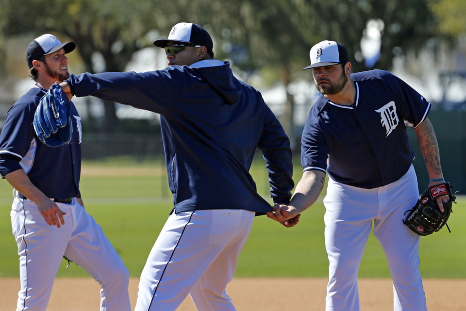 Photo - Detroit Tigers pitcher Anibal Sanchez, center, winds up during a drill as pitcher Joba Chamberlain, right, grabs him from behind with pitcher Joe Natan, left, looking on during the team's first day of baseball spring training for pitchers and catchers, in Lakeland, Fla., Friday, Feb. 14, 2014. (AP Photo/Gene J. Puskar)
