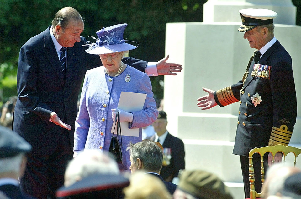 Photo - FILE - In this June 6, 2004 file photo, French President Jacques Chirac, left, greets Queen Elizabeth II, of Britain, and her husband Prince Philip at the British military cemetery in Bayeux, northwestern France, during ceremonies marking the 60th anniversary of the D-Day landings in Normandy. The perils of World War II directly shaped the lives of Elizabeth, 88, and Philip, 92. The anniversary is so heartfelt that the royal couple is preparing to cross the English Channel once more, this time on a Eurostar train through the Channel Tunnel Elizabeth helped 20 years ago. (AP Photo/Michel Spingler, File)