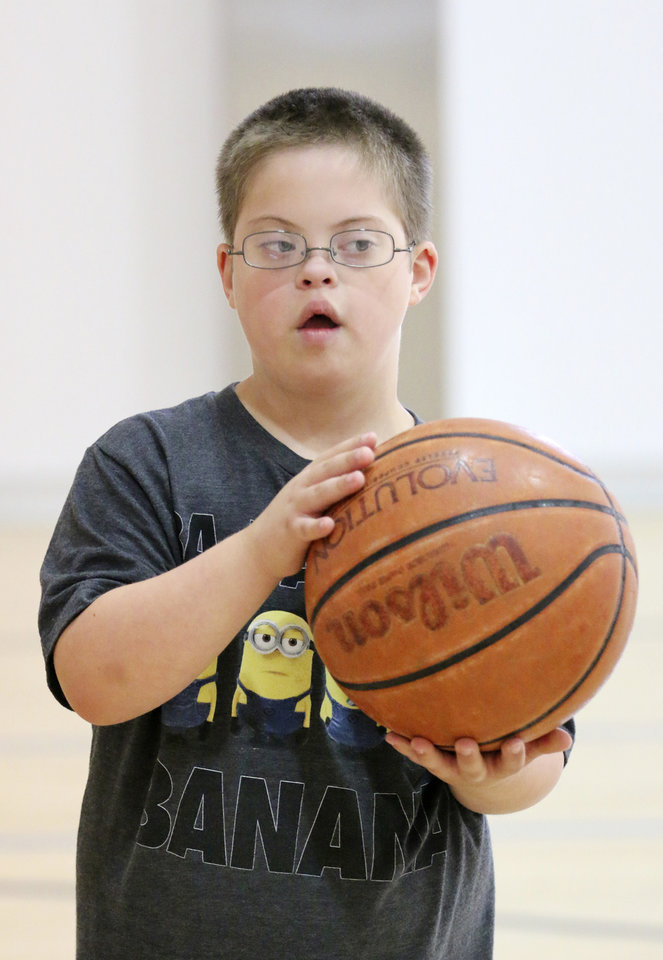 Photo - Will Shipley, 9, practices passing the ball during a Down Syndrome Association of Central Oklahoma basketball camp at Chesapeake Energy's fitness center in Oklahoma City, Friday July  25 , 2014. Photo By Steve Gooch, The Oklahoman