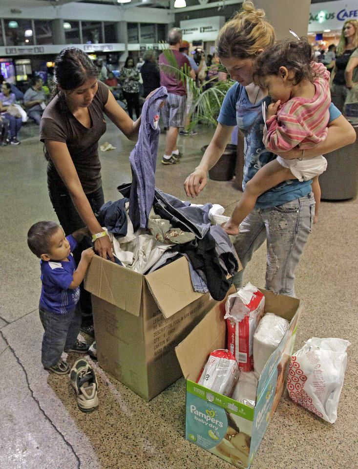 Photo - Women and children look through a box of cloths that were donated by volunteers at the Greyhound bus terminal, Thursday, May 29, 2014 in Phoenix.  About 400 mostly Central American women and children caught crossing from Mexico into south Texas were flown to Arizona this weekend after border agents there ran out of space and resources.  Officials then dropped hundreds of them off at Phoenix and Tucson Greyhound stations, overwhelming the stations and humanitarian groups who were trying to help. (AP Photo/Rick Scuteri)