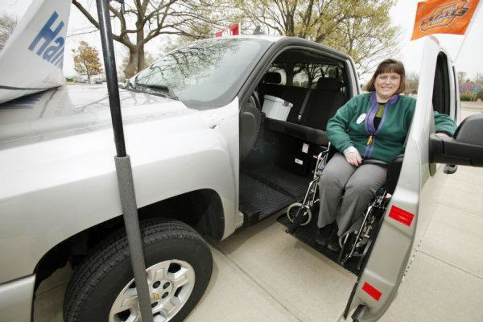 AgrAbililty Program Assistant Stacy Bauter demonstrates a GoShichi wheel chair lift on a converted Chevrolet Silverado pickup Monday at the Capitol. <strong>Steve Gooch - The Oklahoman</strong>