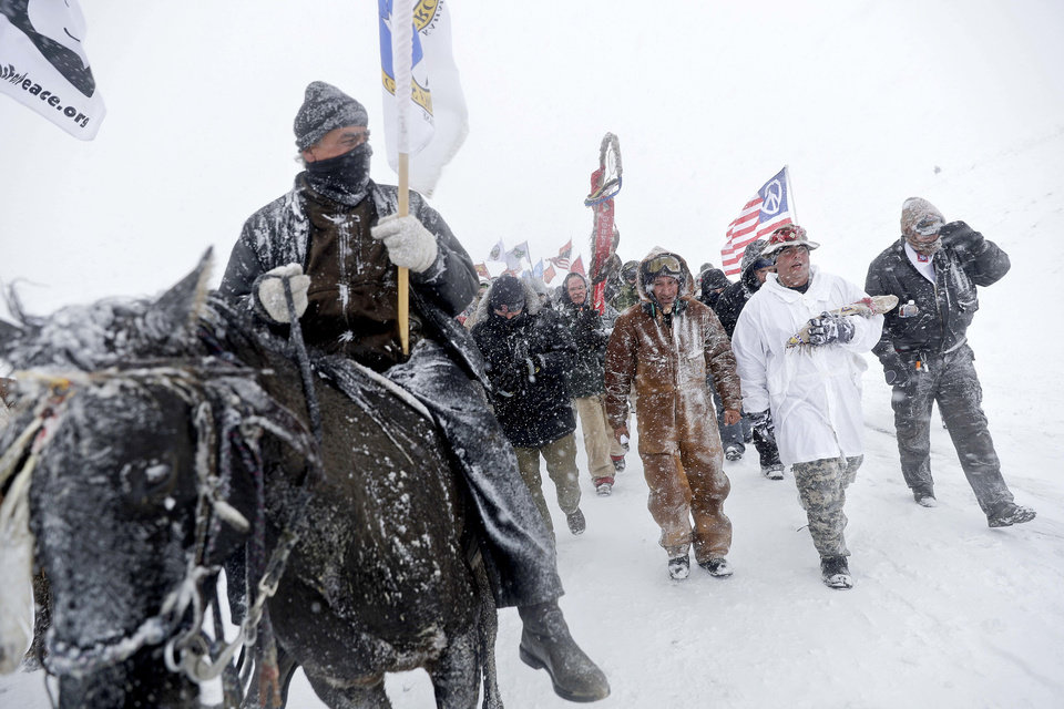 Photo - Military veterans and Native American tribal elders march to a closed bridge outside the Oceti Sakowin camp where people have gathered to protest the Dakota Access oil pipeline in Cannon Ball, N.D., Monday, Dec. 5, 2016. (AP Photo/David Goldman)