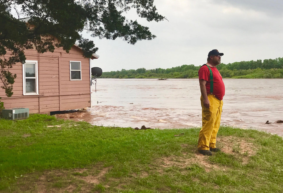 Photo - Member of the Twin Lake Fire Dept. watches water in The Cimarron River rush by as it washes away the dirt under a home in the Twin Lakes Area. [Chris Landsberger/The Oklahoman]