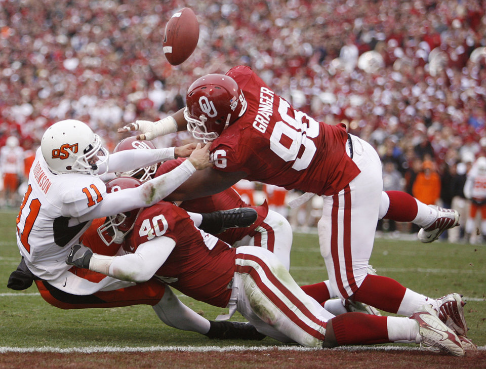 Photo - BEDLAM, FUMBLE: Oklahoma State's Zac Robinson (11) fumbles the ball as he is brought down by Oklahoma's Curtis Lofton (40) and DeMarcus Granger (96) on a fourth down play during the first half of the college football game between the University of Oklahoma Sooners (OU) and the Oklahoma State University Cowboys (OSU) at the Gaylord Family -- Oklahoma Memorial Stadium on Saturday, Nov. 24, 2007, in Norman, Okla.  Photo By Bryan Terry, The Oklahoman ORG XMIT: KOD