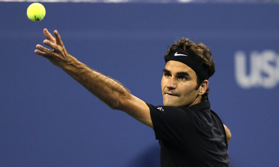 Photo - Roger Federer, of Switzerland, tosses the ball on a serve against Roberto Bautista Agut, of Spain, during the fourth round of the 2014 U.S. Open tennis tournament, Tuesday, Sept. 2, 2014, in New York. (AP Photo/Charles Krupa)